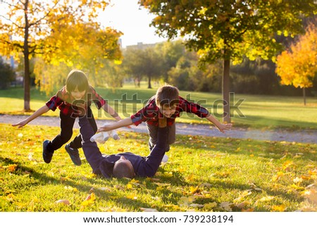 Cute funny children, playing with their father in the park, autumn time, nice afternoon back light