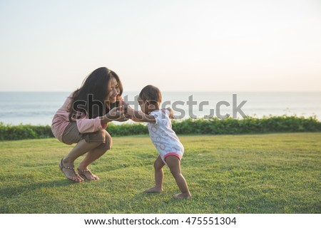 Cute funny happy baby making his first steps on a green grass, mother holding her hands supporting by learning to walk