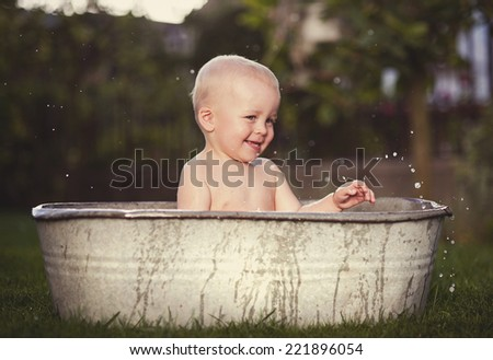 Cute funny little boy bathing in galvanized tub outdoor in green garden - stock photo