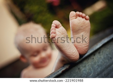 Cute funny little boy bathing in galvanized tub outdoor in green garden, close up of feet - stock photo