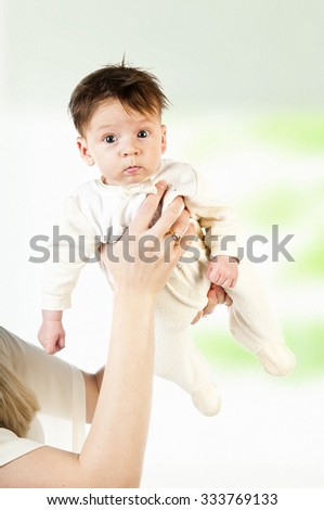 Cute funny little boy in hands of mother
