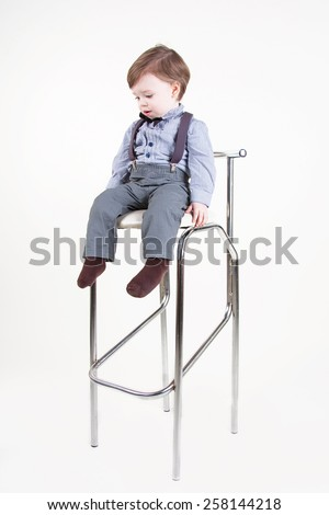Cute funny little boy sitting on a chair and and looking down - stock photo