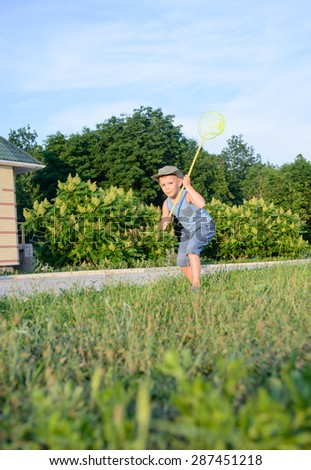 Cute funny little boy wearing hat, sleeveless top and short pants, while running to catch butterflies with a net on the green lawn in a warm day of summer - stock photo