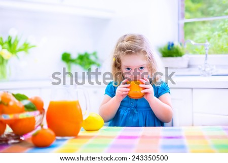 Cute funny little girl drinking freshly squeezed orange juice for healthy breakfast in a white kitchen with window on a sunny summer morning - stock photo