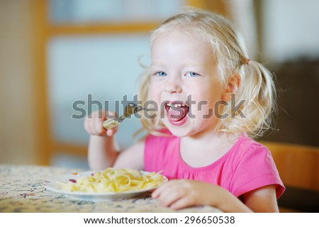Cute funny little girl eating spaghetti