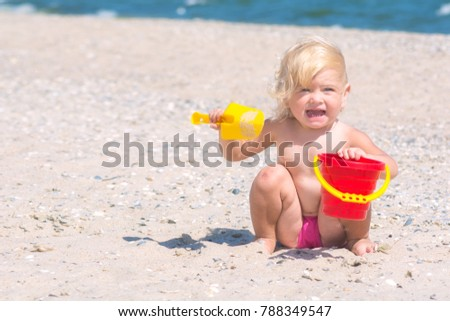 Cute funny little girl playing with toy buckets and spade in sand on sea beach.