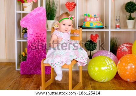Cute funny little kid in first birthday with colored balloons in the bright room - stock photo