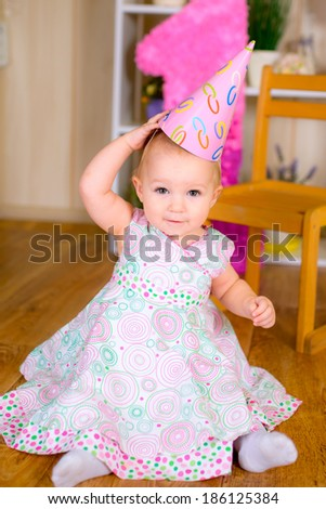Cute funny little kid in first birthday with colored balloons in the room - stock photo