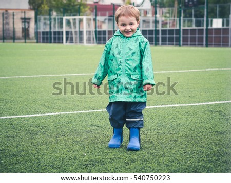 Cute funny little kid playing on the playground in a beautiful green cloak with dinosaurs. Sport, bad weather, rain.