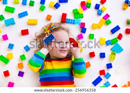 Cute funny preschooler little girl in a colorful shirt playing with construction toy blocks building a tower in a sunny kindergarten room. Kids playing. Children at day care. Child and toys. - stock photo