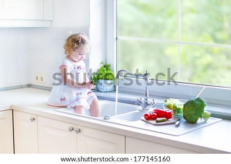 Cute funny toddler girl washing vegetables in a kitchen sink helping her mother to cook salad for lunch in a beautiful white kitchen with a big window with garden view - stock photo