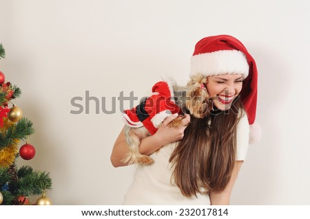 cute funny woman in Santa hat with toy terrier on Christmas tree background - stock photo