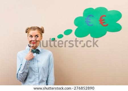 Cute geek girl is thinking about money. Hmmm money... - stock photo