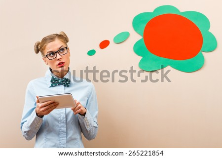Cute geek girl is thinking about something while using digital tablet.Geek girl using digital tablet - stock photo