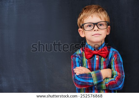 Cute ginger boy standing against blackboard background - stock photo