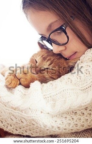 Cute ginger cat sleeps warming in knit sweater on his owner's hands - stock photo