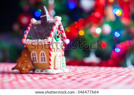 Cute gingerbread cookie and candy ginger house background Christmas tree lights - stock photo