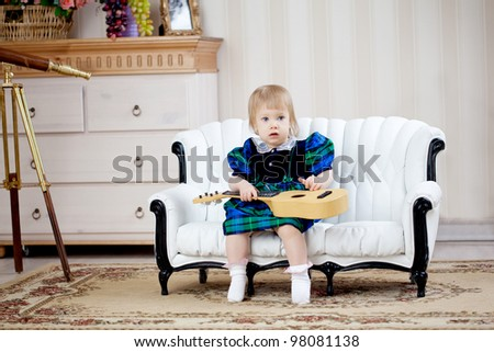 Cute girl, a child in a blue dress with guitar - stock photo