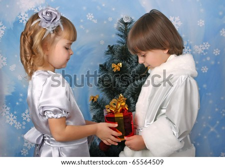 cute girl and a boy near a Christmas tree with gift in hand