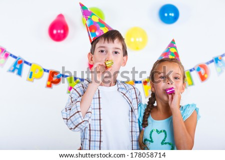 Cute girl and boy having fun at birthday party