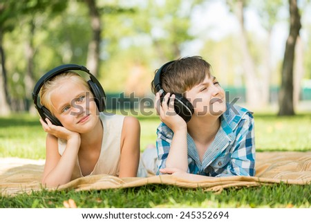 Cute girl and boy lying in park and listen to music - stock photo