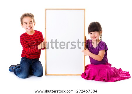 Cute girl and boy pointing and sitting near blank ad board - stock photo