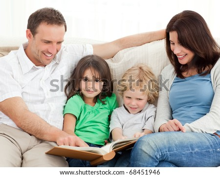 Cute girl and her family looking at a photo album on the sofa
