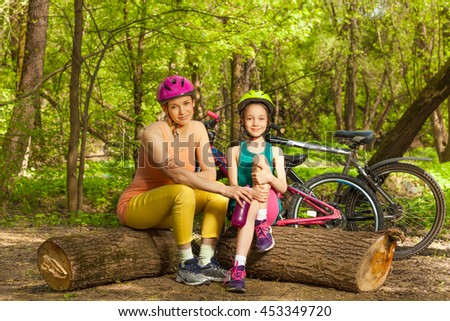 Cute girl and her mom having rest on logs - stock photo