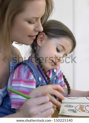 Cute girl and mother coloring book together at home - stock photo
