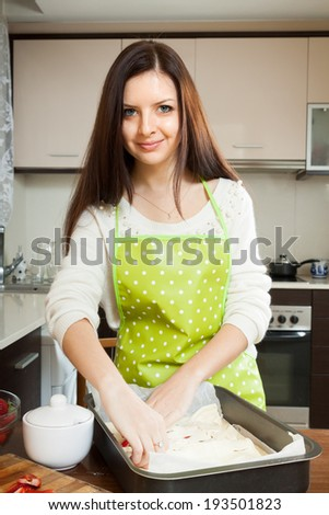 Cute  girl at  table cooking  strawberry pie