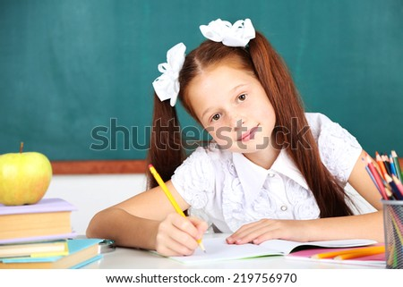 Cute girl at workplace in classroom - stock photo