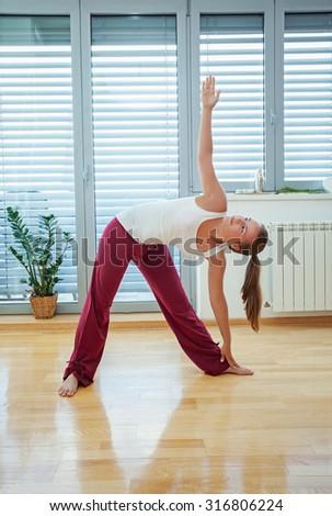 Cute girl, beginner in yoga, doing her exercise at home - stock photo