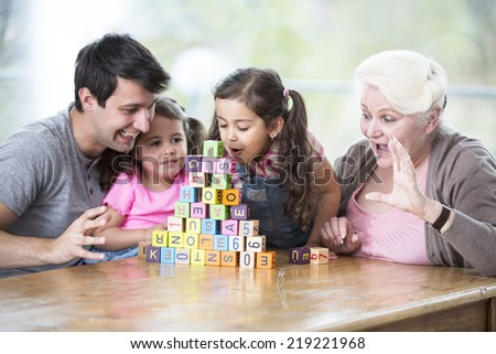 Cute girl blowing alphabet blocks while family looking at it in house - stock photo