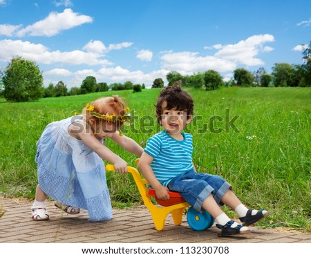 cute girl carrying her brother in the cart - stock photo