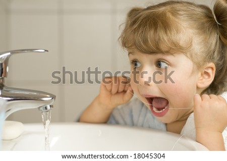 Cute girl cleaning teeth by floss in bathroom - stock photo