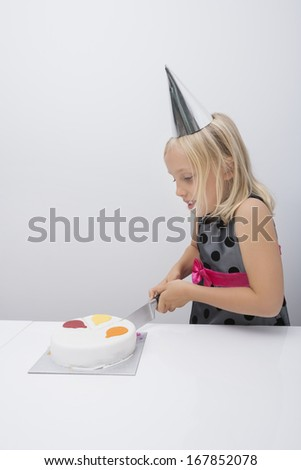 Cute girl cutting birthday cake at table in house - stock photo