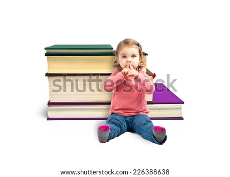 Cute girl doing silence gesture around books
