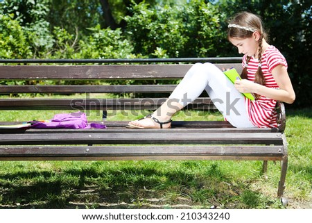 Cute girl drawing on bench in park - stock photo