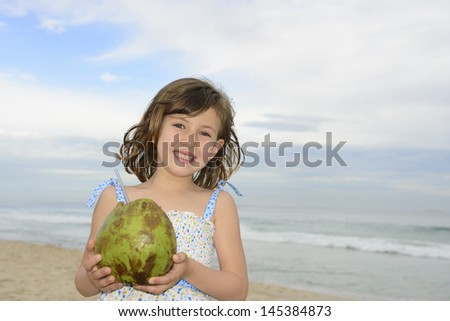 cute girl drinking coconut water on beach