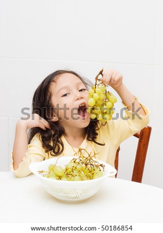 cute girl eating grapes - stock photo
