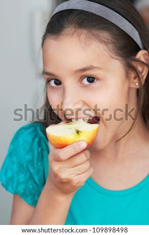 cute girl eats an red apple