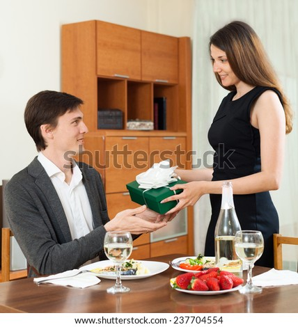 Cute girl gives her man a gift during dinner - stock photo