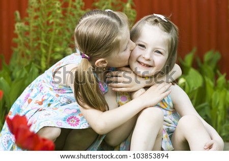 Cute girl giving a kiss to her younger sister - stock photo