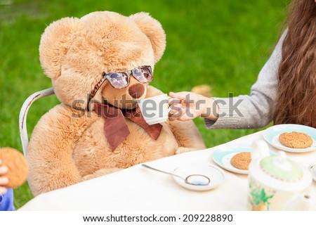 Cute girl giving tea to teddy bear at yard - stock photo