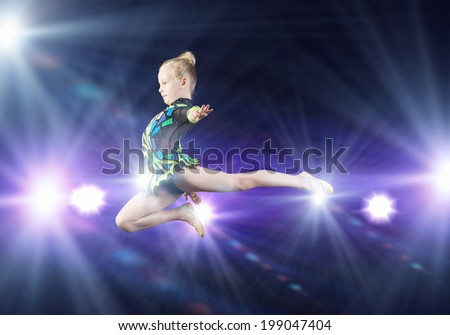 Cute girl gymnast in performance costume jumping high - stock photo
