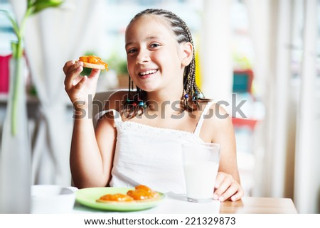 Cute girl having breakfast and drinking milk, at home