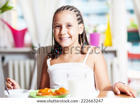 Cute girl having breakfast, at home