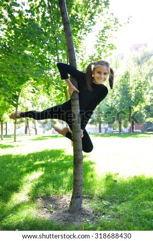 Cute girl having fun outdoor training uses a tree as a gymnastic pole.  - stock photo