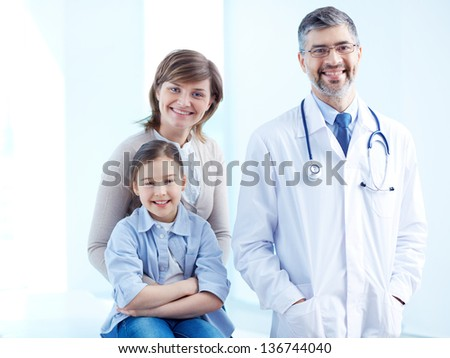 Cute girl, her mother and doctor looking at camera - stock photo