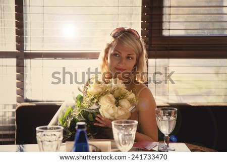 Cute girl holding a bouquet of flowers in a restaurant - stock photo
